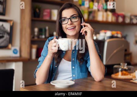 Sorridente giovane donna parla al telefono cellulare presso il cafe. Cracovia in Polonia Foto Stock