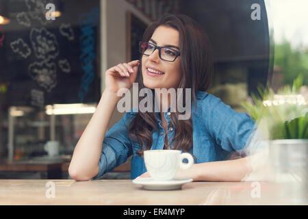Bella donna che indossa gli occhiali di moda presso il cafe. Cracovia in Polonia Foto Stock