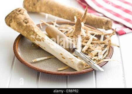 Sbucciate radice di rafano su piastra Foto Stock