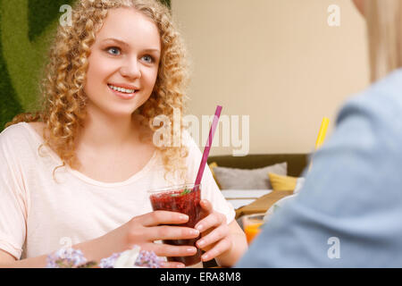 Sorridente ragazza con cocktail in cafe Foto Stock