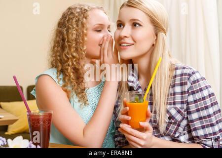 Ragazza raccontare segreti per il suo amico in cafe Foto Stock