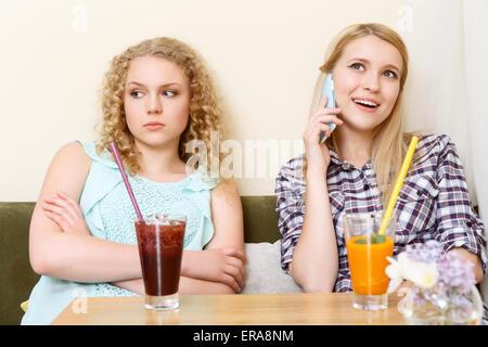 Ragazza utilizzando il telefono cellulare in cafe Foto Stock