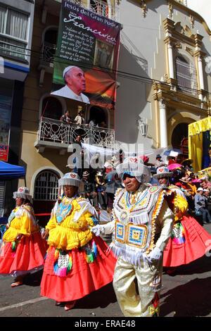 La Paz, Bolivia, 30 maggio 2015. Ballerini Kullaguada passare un banner di Papa Francesco appendere fuori del Santuario Foto Stock