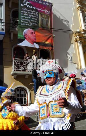 La Paz, Bolivia, 30 maggio 2015. Un ballerino kullaguada passa un banner di Papa Francesco durante sfilate per il Foto Stock