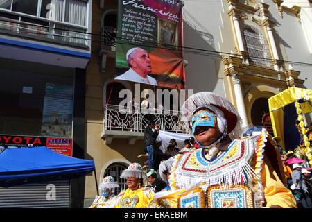 La Paz, Bolivia, 30 maggio 2015. Un ballerino kullaguada passa un banner di Papa Francesco appendere fuori del Santuario Foto Stock