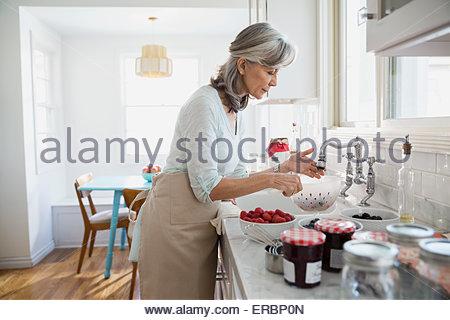 Donna fare jam con frutti di bosco freschi in cucina Foto Stock