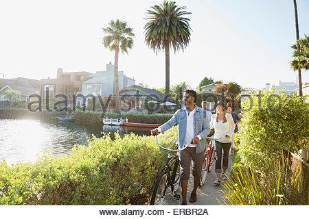 Amici a piedi biciclette sul percorso lungo il canale di sole Foto Stock