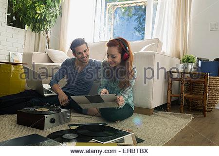 Coppia con ascolto in cuffia in vinile a soggiorno Foto Stock
