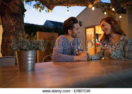 Affettuosa giovane bevendo vino tenendo le mani sul patio Foto Stock