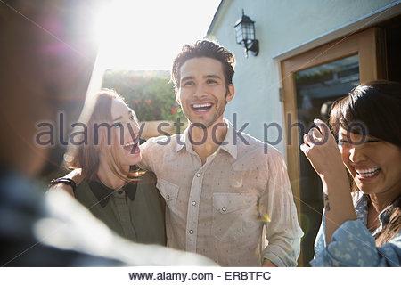Gli amici di ridere sul patio soleggiato Foto Stock