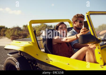Emozionato felice coppia godendo di viaggio su strada in loro automobile. L uomo alla guida della vettura giovane donna prendendo un selfie dal suo telefono cellulare. Foto Stock