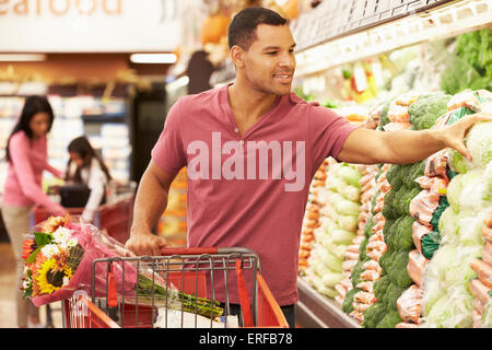 Uomo carrello di spinta da produrre contatore nel supermercato Foto Stock