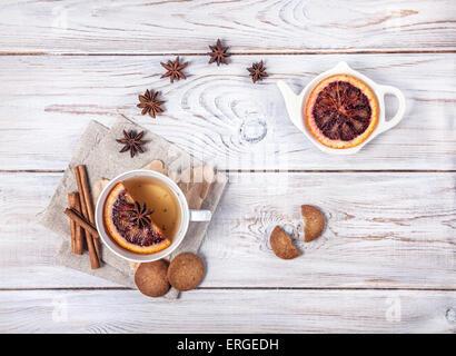 Tè marocchino con spezie e fetta di arancione sul bianco sullo sfondo di legno Foto Stock