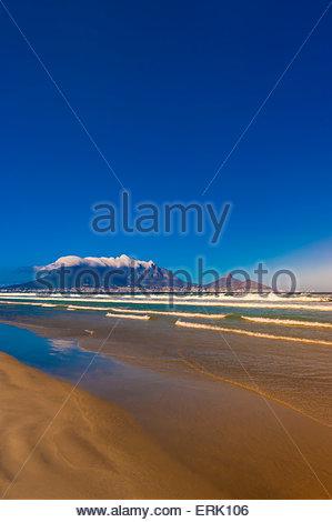 Vista di Città del Capo e di Table Mountain e testa di leone Peak dalla spiaggia di Milnerton, Sud Africa. Foto Stock