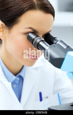 Close up di scienziato guardando al microscopio in laboratorio Foto Stock