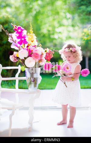Bambina disponendo dei fiori a casa in un vaso. Bambini che giocano al chiuso. Kids festa di compleanno. I bambini Foto Stock