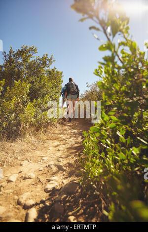 Immagini di persone a piedi attraverso il sentiero di montagna. Vista posteriore del colpo di escursionismo coppia Foto Stock