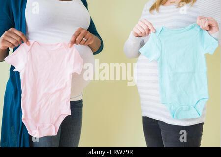 Donne in stato di gravidanza tenendo un ragazzo e una ragazza vestiti del bambino Foto Stock