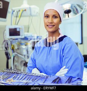 Ritratto di fiducioso chirurgo vicino a forbici chirurgiche in sala operatoria Foto Stock