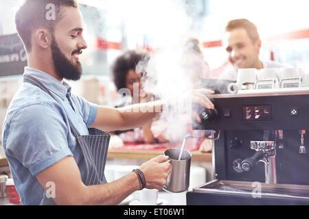 Barista per la cottura a vapore nel latte cafe Foto Stock