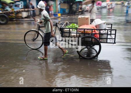 L'uomo trascinando il triciclo con bagagli su strada in Kolkata a West Bengal India Asia Foto Stock