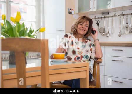 Felice senior donna avente una tazza di tè e parlando al cellulare in cucina, Monaco di Baviera, Germania