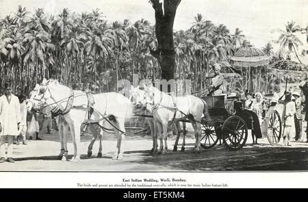 Old vintage 1900 sposa indiana e sposo in carrozza a cavallo sotto ombrello tradizionale , Worli , Bombay , Mumbai , Maharashtra , India , Asia Foto Stock