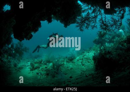 Un subacqueo esplora la bocca di una profonda grotta in Raja Ampat, Indonesia. Foto Stock