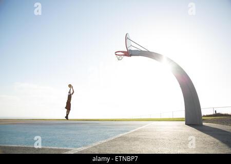 Giovane uomo giocando a basket in un parco di Los Angeles, California, Stati Uniti d'America Foto Stock
