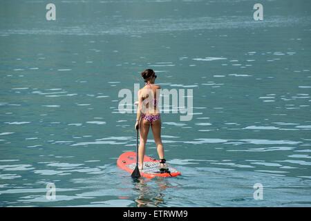 Donna in bikini Stand Up Paddle surf o paletta permanente imbarco sul lago di Annecy in Francia Foto Stock