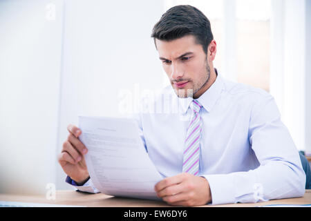 Imprenditore bello sedersi al tavolo di lettura di documenti office Foto Stock