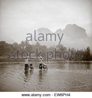 Due donne che indossano conica cappelli asiatici spingere le biciclette attraverso un fiume poco profondo in Vang Foto Stock