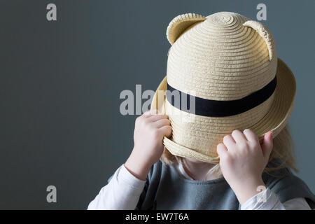 Ragazza tirando il suo cappello verso il basso sopra il suo volto Foto Stock