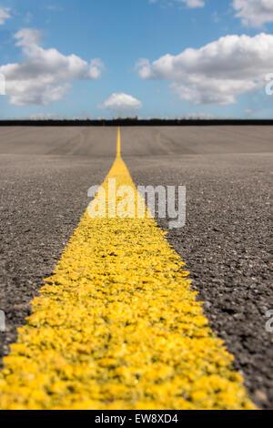 Vista orizzonte di strada texture con striscia gialla. Foto Stock