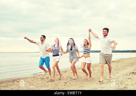 Sorridente amici in occhiali da sole in esecuzione sulla spiaggia Foto Stock