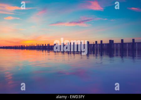 Splendido oceano scena con molo in legno al tramonto Foto Stock