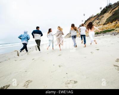 Un gruppo di giovani uomini e donne in esecuzione su una spiaggia, divertimento Foto Stock
