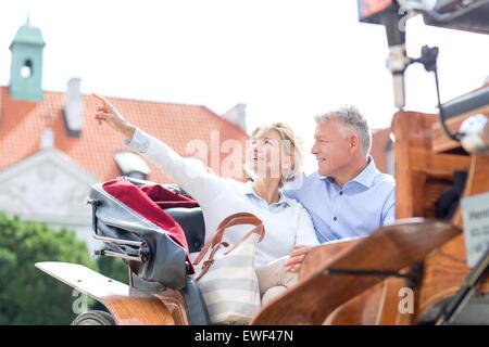 Donna di mezza età che mostra qualcosa da uomo mentre seduto a cavallo carrello Foto Stock