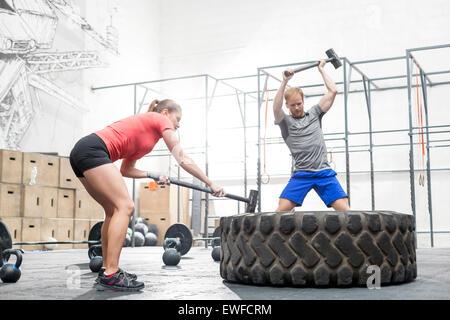 L uomo e la donna di colpire il pneumatico con la mazza in palestra crossfit Foto Stock