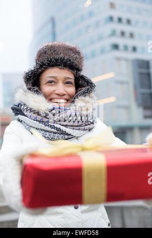 Donna felice azienda dono durante il periodo invernale in città