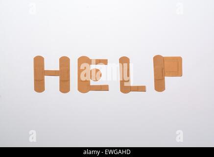 Bende formante la parola help su sfondo bianco Foto Stock