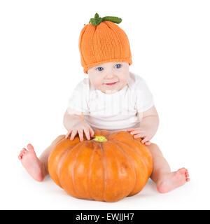 Divertente ridere little baby sitting e giocando su una zucca enorme di indossare una maglia zucca hat su sfondo bianco Foto Stock