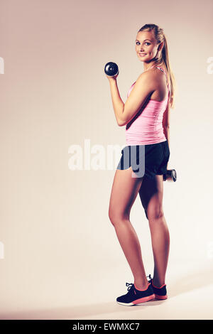 Giovane donna che indossa abiti da allenamento e sorridente in posa tenendo pesi liberi. Foto Stock