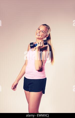 Giovane donna sorridente guardando la fotocamera e tenendo un manubrio. Foto Stock