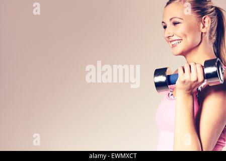 Profilo di giovane donna sorridente e tenendo il manubrio a spalla. Foto Stock