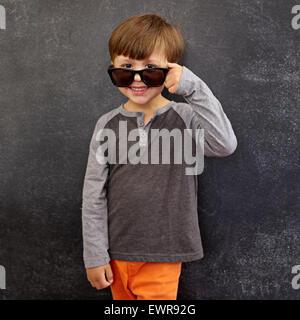 Ritratto di felice little boy indossando occhiali da sole sorride alla telecamera. Piccolo Ragazzo di sbirciare da dietro i suoi occhiali da sole contro la lavagna.