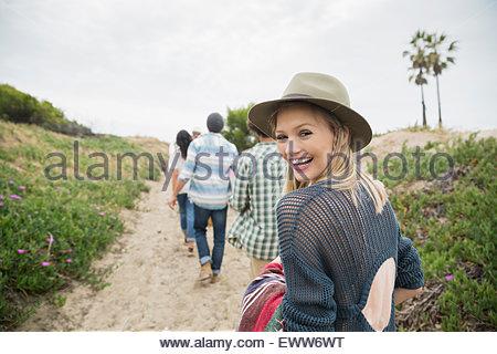 Ritratto sorridente giovane donna camminando sul percorso spiaggia Foto Stock