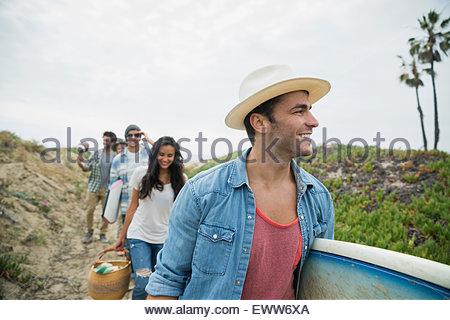 Gli amici che trasportano le tavole da surf sul percorso spiaggia Foto Stock