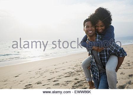 Giovane piggybacking di sunny beach Foto Stock