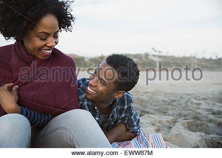Coppia sorridente rilassante sulla spiaggia Foto Stock